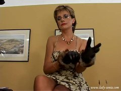 Lady Sonia in fur gloves playing with a slave