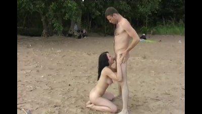 Titted brunette sucks on the beach