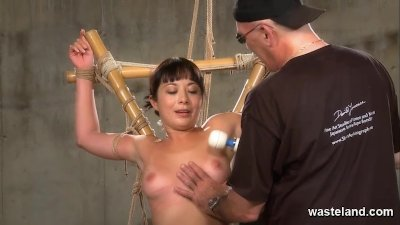 She is tied up suspended and flogged by BDSM master