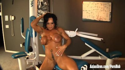 Big beautiful bodybuilder flexes her muscles in the gym, strips then plays